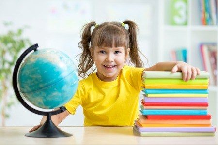 schooler: smiling kid girl with globe and books
