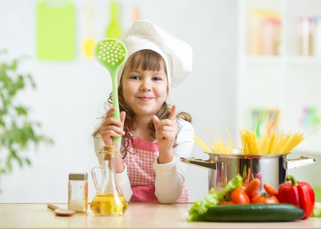 Kid girl cook makes healthy vegetables meal in the kitchen photo