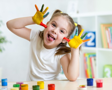 Kid girl having fun, her palms covered with paint Stock Photo
