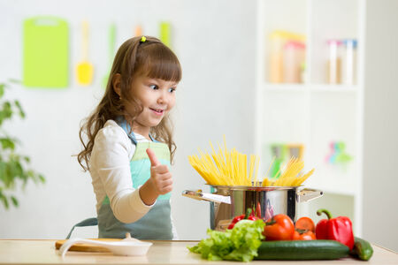 a little dinner: child girl playing cook and preparing healthy food