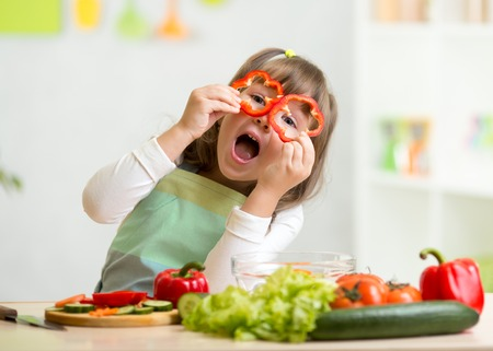 meal preparation: kid girl having fun with food vegetables at kitchen