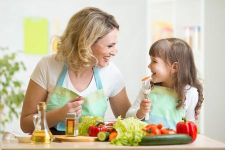 mujeres cocinando: la madre y el niño de preparar la comida saludable y divertirse