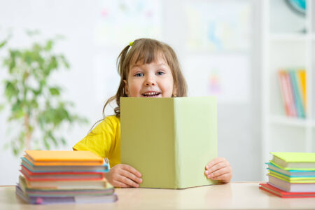 one story: kid girl with open book studying in primary school