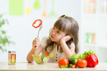 discontent: pretty kid girl refusing to eat her dinner healthy vegetables