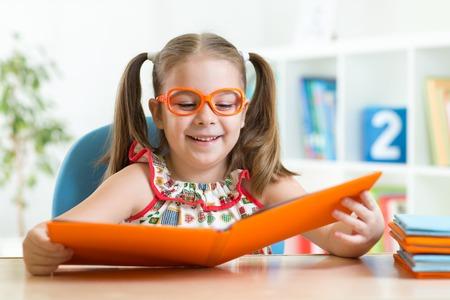 hyperopia: Happy funny kid girl in eyeglasses reading a book Stock Photo