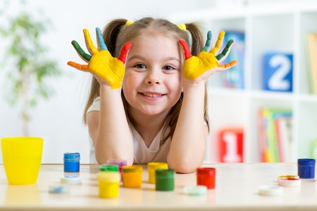 children painting: Portrait of kid girl with face and hands painted at home Stock Photo