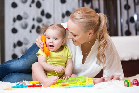 baby playing toy: child girl phone with mother playing with toy phone Stock Photo