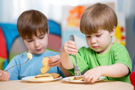 kasha: children eating healthy food at home or kindergarten