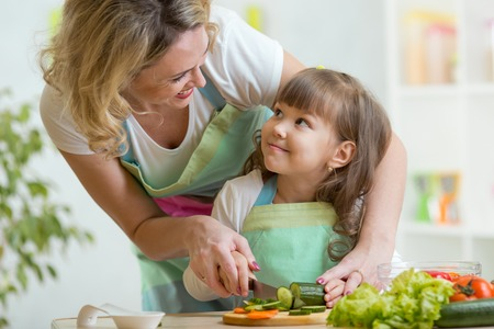kitchen aprons: mother and kid girl cooking and cutting vegetables on kitchen Stock Photo