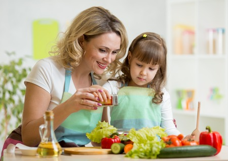 mother with kid make vegetable salad at kitchen photo