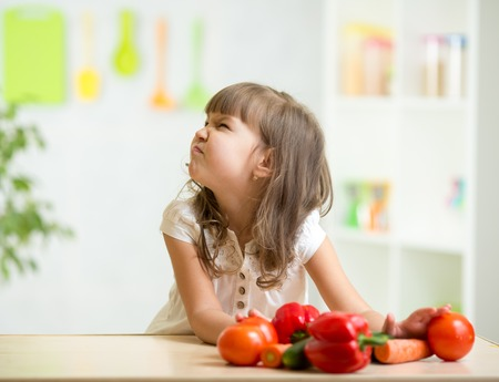disgust: child girl with expression of disgust against vegetables Stock Photo