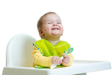 baby eating: funny baby child sitting in chair with a spoon isolated