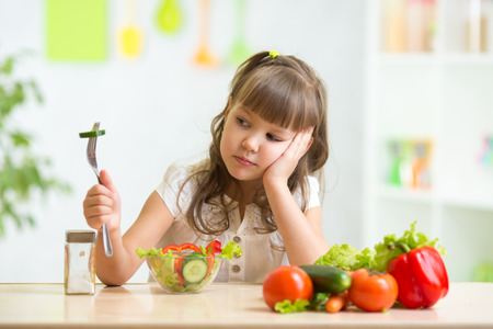 eten: Kind meisje kijkt met afschuw voor gezonde voeding