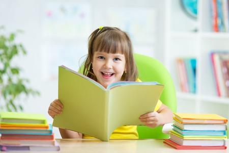 colegiala: Muchacha feliz del ni�o con el libro abierto en la guarder�a