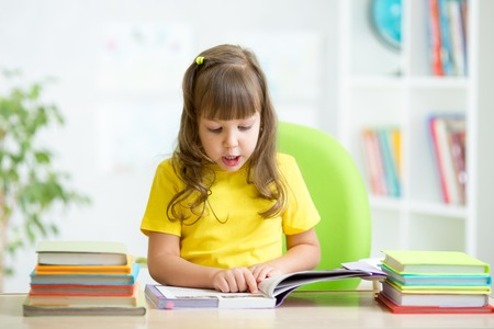 child reading: Happy child girl reading book at table in nursery Stock Photo