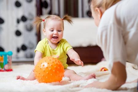 bebe gateando: mamá jugando a la pelota con el bebé de interior en casa