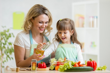 beautiful salad: mom and kid girl preparing healthy food at home