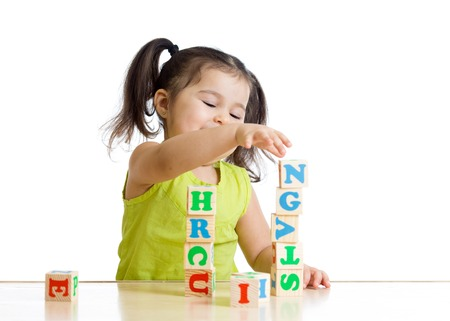 Little kid girl playing with wooden blocks with letters