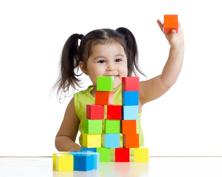 kid girl plays with building blocks and shows red cube