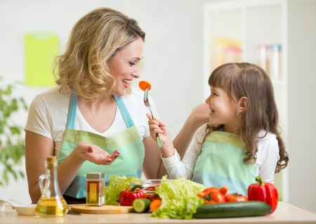 healthy person: kid and mother eating healthy food vegetables