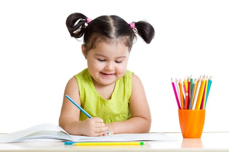 Cute kid drawing with colorful pencils and smiling, isolated on white photo