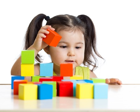toddler kid girl builds a tower with colorful blocks