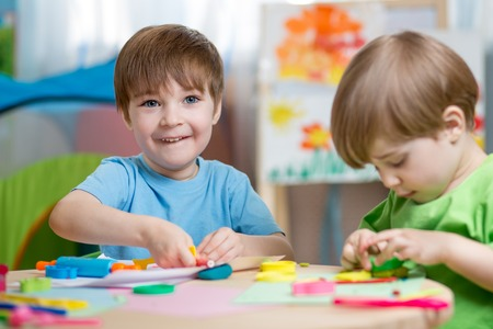 ni�os inteligentes: muchachos de los ni�os con juguetes juego de arcilla en el hogar