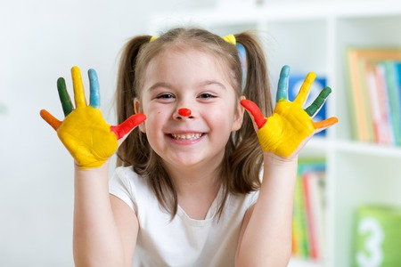 cute cheerful child girl with painted hands and face photo