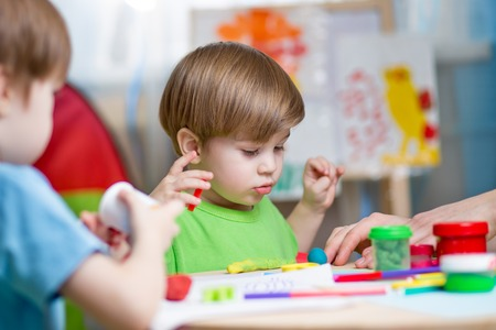 niños jugando: niños jugando con plastilina en casa o guardería