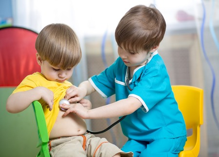 child boy weared as doctor role playing with his younger brother