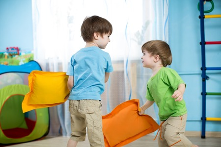 kids room: Two children boys playing with pillows at home