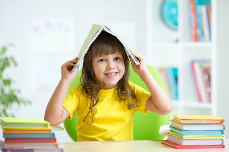 smiling child girl with a book over her head in primary school photo
