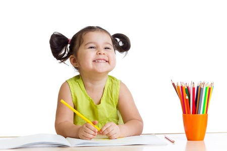 happy kid girl drawing with colourful pencils photo