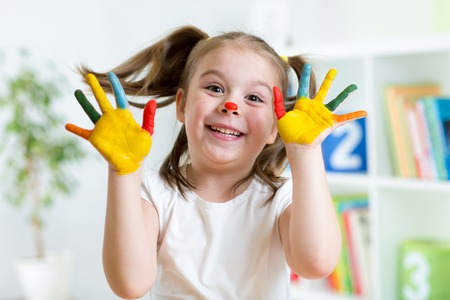 Funny kid girl with hands painted in colorful paint photo