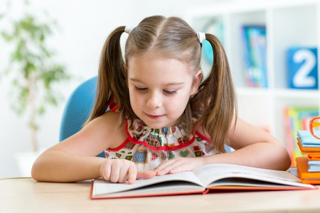 smiling kid student girl reading book in children room Stock Photo