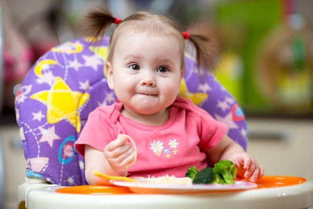 baby with spoon: cute kid girl eating in high-chair on kitchen Stock Photo