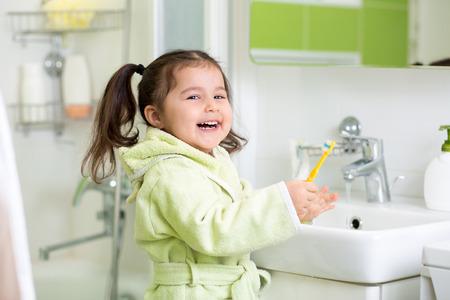 diente: Muchacha sonriente ni�o cepillarse los dientes en el ba�o