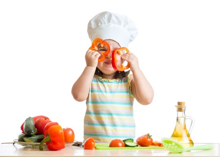 Funny chef kid girl cooking at kitchen photo