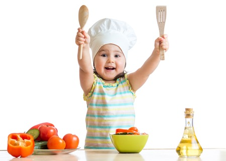 vegetable cook: Smiling kid cook with ladle and kitchen spatula , isolated on white