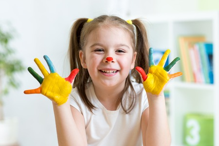 playschool: cute cheerful kid with painted hands and face