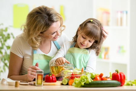 healthy person: mom and kid girl preparing healthy food at home