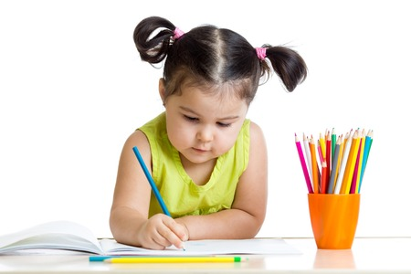 girl child: Cute child drawing with colorful crayons isolated on white Stock Photo