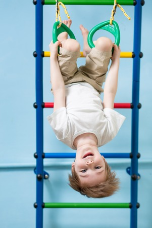 gymnastics equipment: child boy hanging on gymnastic rings at home Stock Photo