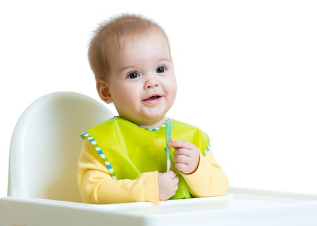 cheerful happy baby child sitting in chair with a spoon photo