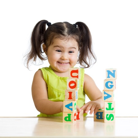 children playing with toys: smiling kid little girl is building a toy block sitting at table