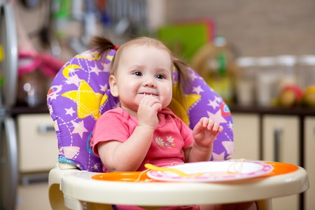 Pretty child toddler eating spaghetti at home