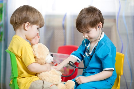 animal doctor: kids brothers playing doctor with plush toy Stock Photo
