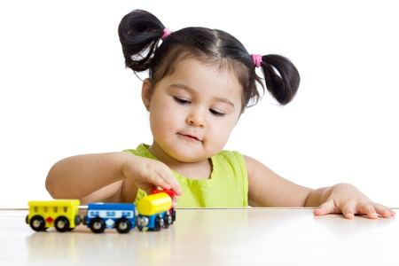young girl: Cute kid girl playing wooden trains toy