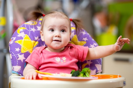 baby eating: cute baby girl eating healthy food on kitchen