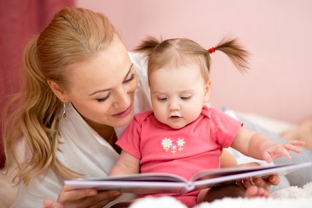 pretty mom reading a book to baby daughter at home Stock Photo